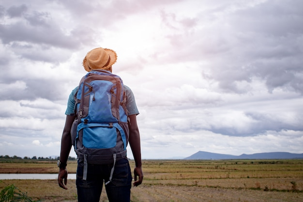Африканский турист путешественник человек с рюкзаком на вид на горы Premium Фотографии