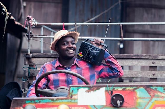 肩にレトロなラジオ放送受信機を持つアフリカの農夫男は古いトラクターの背景に屋外笑顔幸せに立っています。 Premium写真