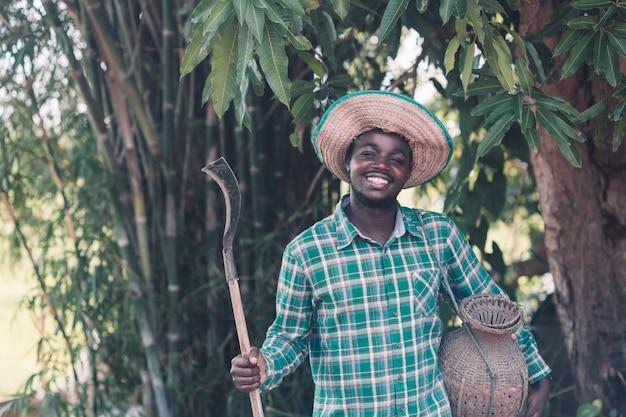 カントリーサイドでナイフを持ってアフリカの農夫男 Premium写真
