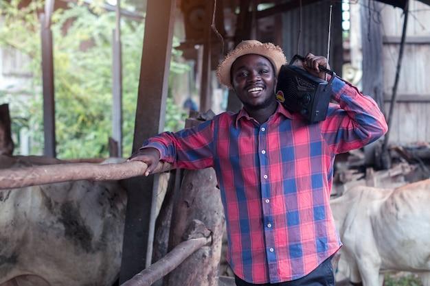 肩にレトロなラジオ放送受信機を持つアフリカの農家の男は、古い牛失速背景に屋外笑顔幸せに立っています。 Premium写真
