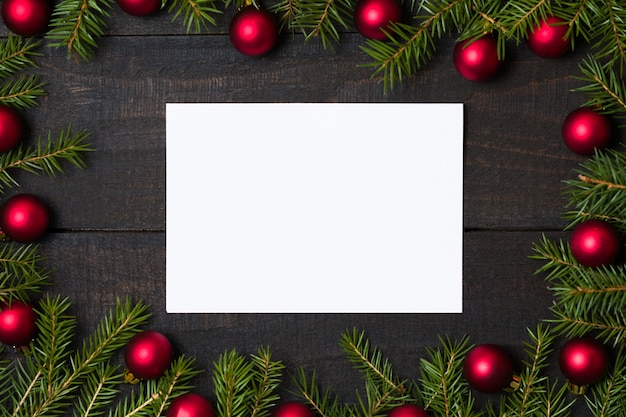 Деревянный фон с белой карточкой и рождественские украшения Premium Фотографии