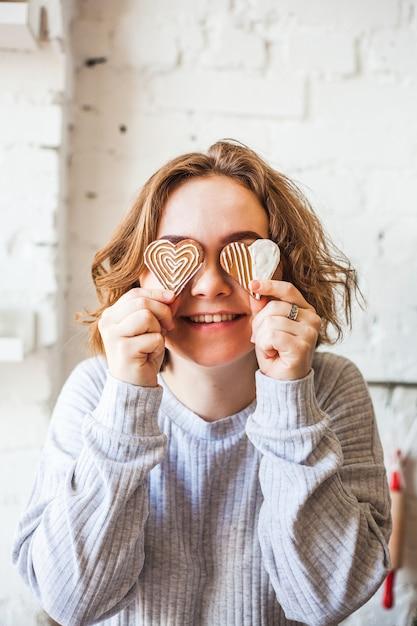 ハート型のクッキー、恋人、バレンタインデー、ベーキング、料理を保持しているヨーロッパ風の女の子 Premium写真