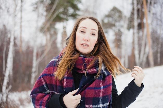 Портрет женщины в зимнем лесу, теплая одежда, шарф Premium Фотографии