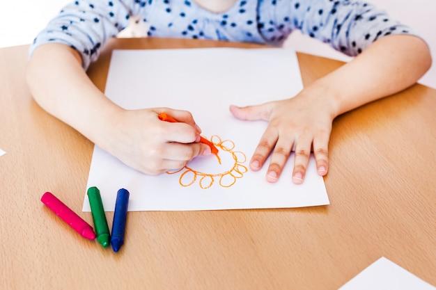 小さくてかわいい女の子がテーブルに座って描く Premium写真