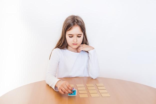Девушка играет в игру, умственные способности, запоминание, настольную игру, играет во время каникул, отдыха, уединения, время с пользой, развивает ум Premium Фотографии