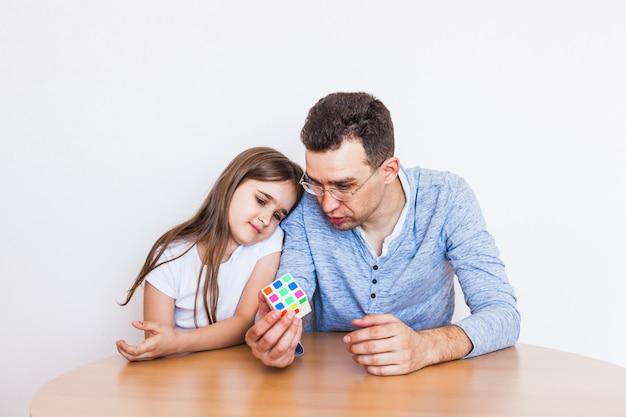 Девочка и папа играют в домашнюю игру, кубик рубика, головоломка для развития мозга Premium Фотографии