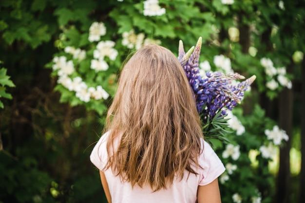 Цветы люпина в руках девушек, красота, изготовление букетов из разных растений, садоводство, детство, интерьер, поле Premium Фотографии