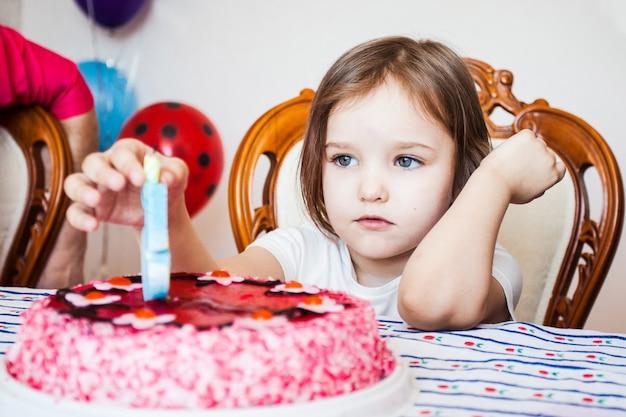 小さな女の子は、誕生日の女の子がケーキの上のろうそくを吹き、友人との誕生日のお祝い Premium写真