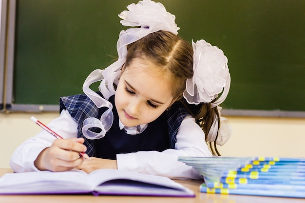 Девочка школьница и школа. девушка носит школьную форму в школе. повышение квалификации Premium Фотографии