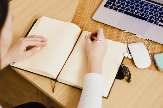 少女は、コンピューターとノートブックを使用して、ビジネスとビジネスを行い、日記に記録を残します Premium写真