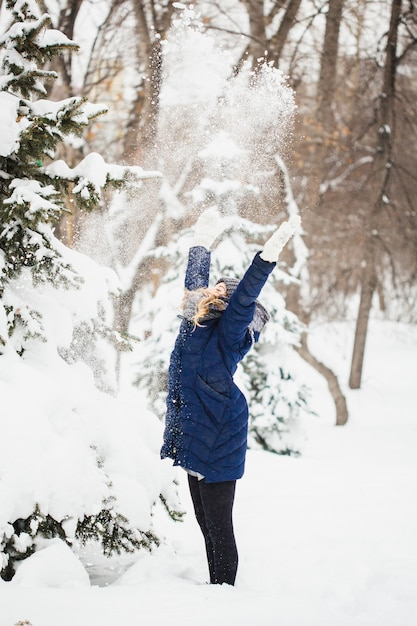 Девушка в зимнем парке покрыта снегом Premium Фотографии