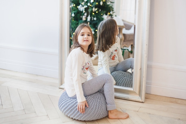 女の子は鏡の近くに座って、鏡はクリスマスツリーとライトを反映しています Premium写真