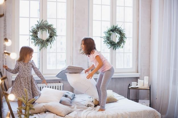 女子、ベッドで枕と戦う姉妹、クリスマスリースで飾られた窓、人生、子供時代 Premium写真