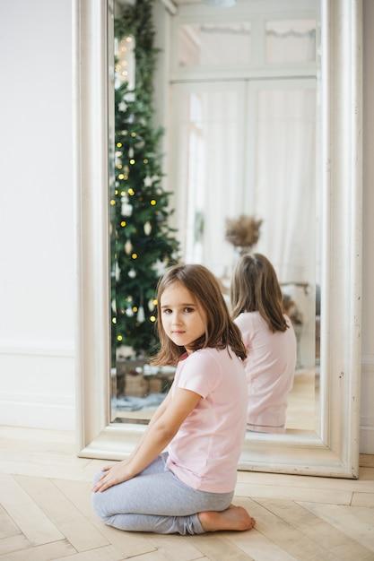 彼は女の子が鏡の近くに座って、鏡はクリスマスツリーとライトを反映し、インテリアは装飾され、クリスマス、休日を待っています Premium写真
