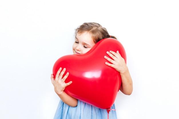 バレンタインの日、恋人、バレンタインの日、家族、心への贈り物に美しい赤いハート形の風船を持った少女 Premium写真