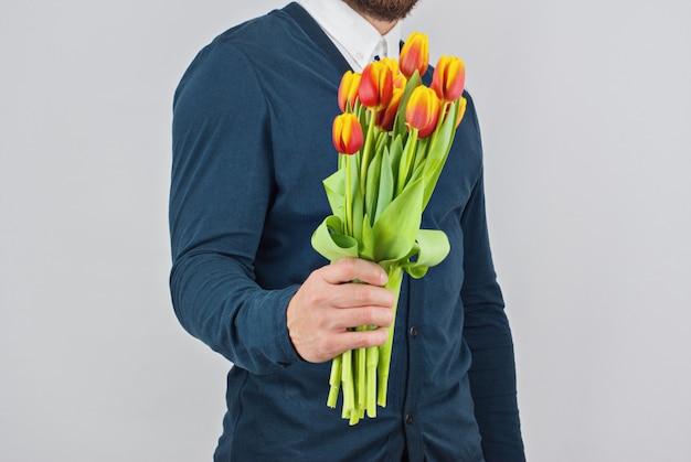Мужчина с бородой держит букет тюльпанов Premium Фотографии