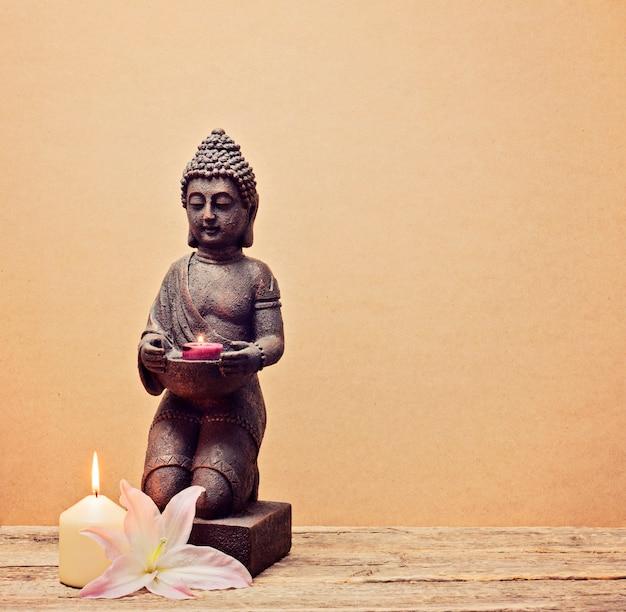 Статуя будды со свечой в руках на деревянном фоне Premium Фотографии