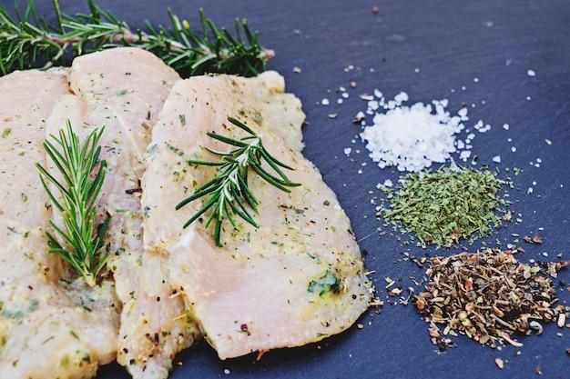 ソースのチキンフィレのスライスと料理、塩、コショウ、ハーブのための様々なスパイス Premium写真