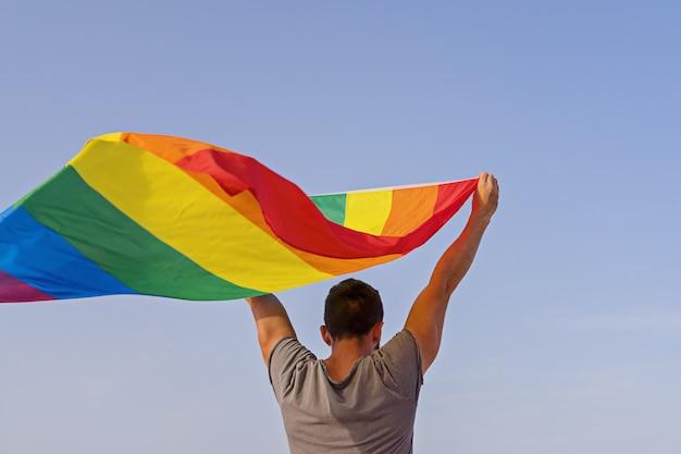 Мужчина держит поднятые руки, размахивая радужным флагом лгбт Premium Фотографии