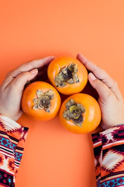 Женская рука держит три спелых хурмы на оранжевый. Premium Фотографии