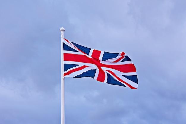 青い曇り空を背景にイギリスの旗を振っています。 Premium写真