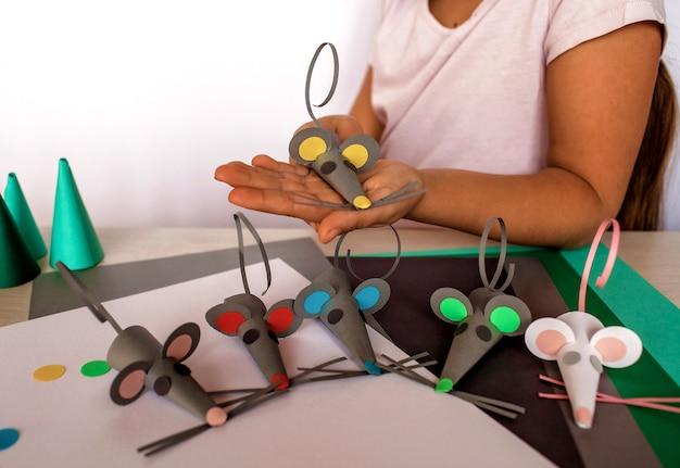 Милая девушка делает мышей с цветной бумагой Premium Фотографии