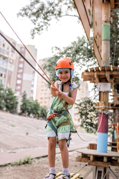 アドベンチャーパークでロープ構造の時間を楽しんでいる女の子 Premium写真