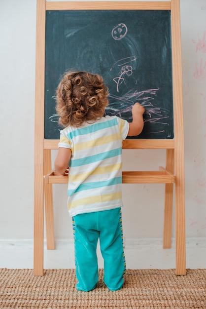 小さな子供は灰色の壁に保育園で自宅の黒いチョークボードにチョークで描画します。 Premium写真