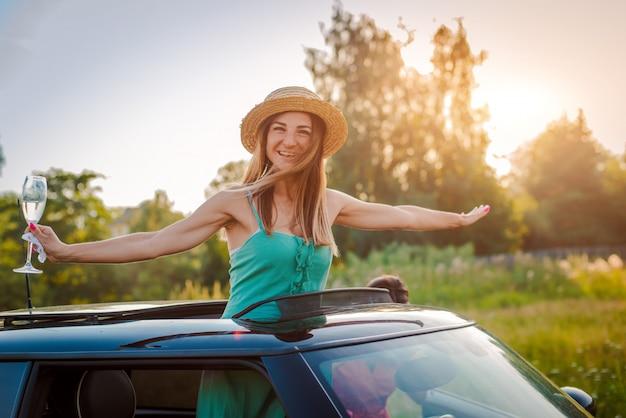 陽気な女の子の女性は、自然の中で夏のパーティーで車のハッチから傾いているワインのグラスと喜んでいます。 Premium写真