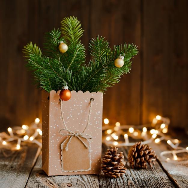 クリスマスの組成物。茶色の木製の紙袋とバンプモミの枝 Premium写真