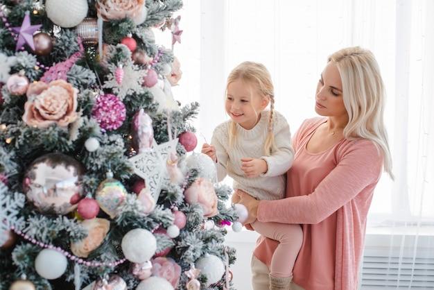 Мама и дочь украшают елку в помещении. Premium Фотографии