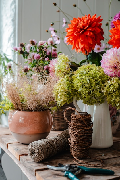 Большой букет из цветочных композиций на рабочий стол флориста на фоне бетонной стены Premium Фотографии