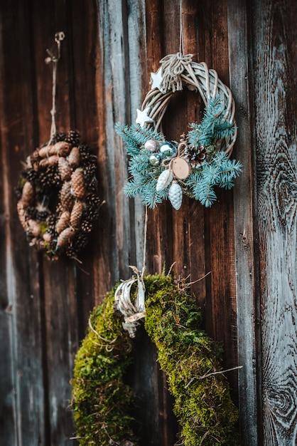 Праздничный деревенский венок из шишек на темно коричневый деревянный фон. концепция рождественских праздников и нового года. Premium Фотографии