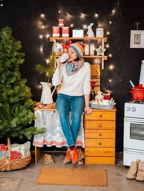 女性の明るい帽子のストーブ。女の子は冬の夜を準備します。黒の背景に木製の素朴なキッチン。 Premium写真