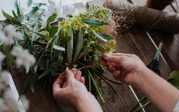 Женский профессиональный флорист готовит композицию из полевых цветов. Premium Фотографии