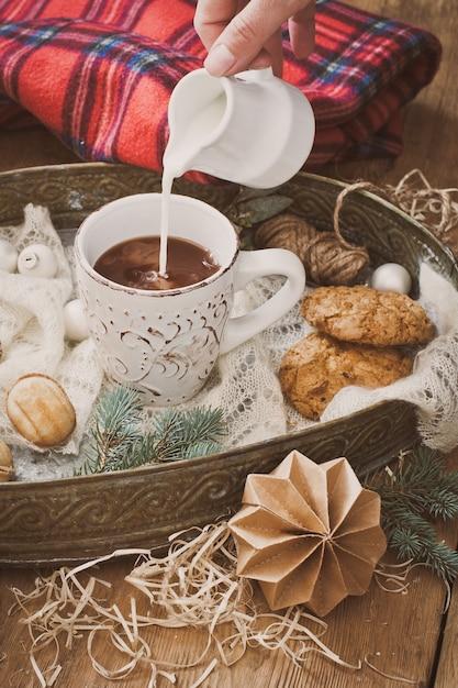 ココアとクリスマスの装飾のマグカップにミルクを注ぐ Premium写真