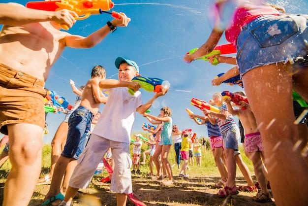 美しい晴れた日に水の大砲と屋外で遊ぶ子供たち Premium写真