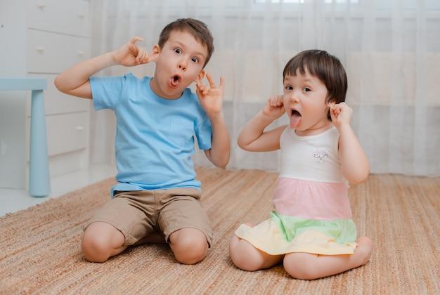 Дети, мальчик девочка, непослушная комната на полу. они гримасничают. Premium Фотографии