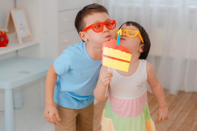 Мальчик и девочка, играя с реквизит бумажный торт со свечой. Premium Фотографии