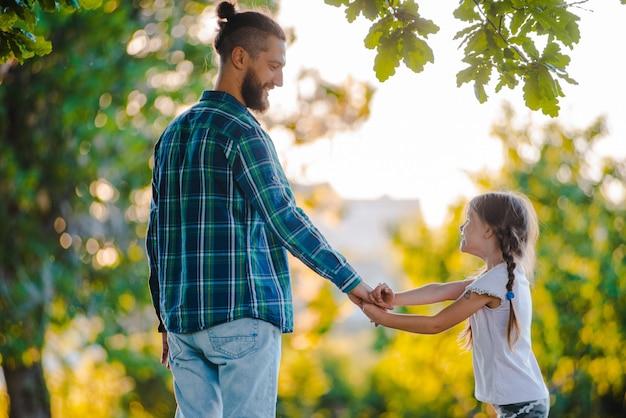 少女の子供の娘が彼女の父の手を握って、夕暮れ時の自然の。 Premium写真