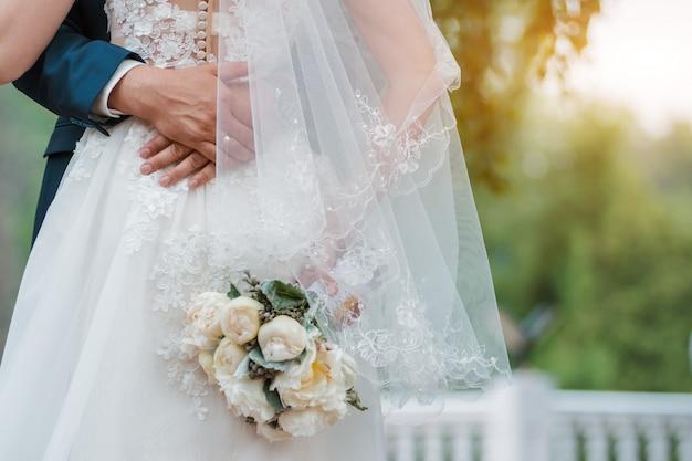 新婚カップル。結婚式の日。手に花嫁の花束、新郎の抱擁。 Premium写真