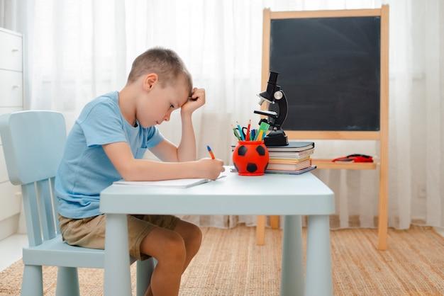 本のトレーニングで満たされた机横になっている家の教室に座っている学校少年 Premium写真
