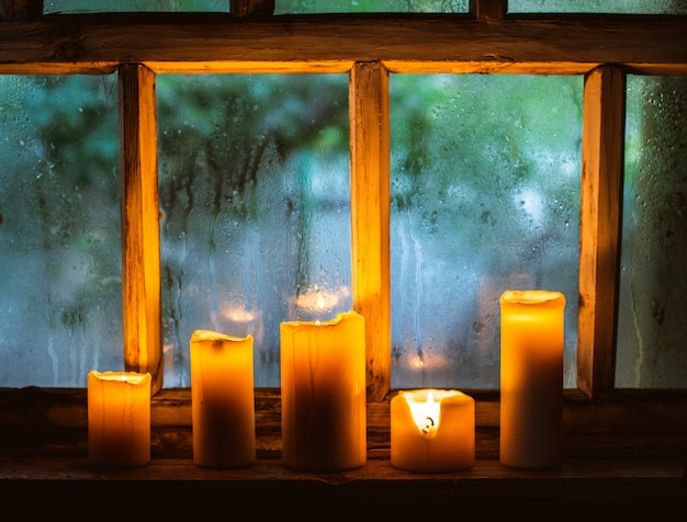 Капли дождя на окне и горящие свечи Premium Фотографии