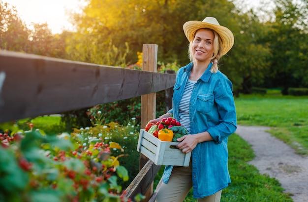 Молодая женщина с коробкой свежих экологических овощей на закате Premium Фотографии