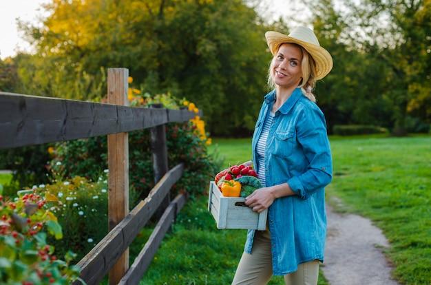 Красивая женщина-фермер в шляпе с коробкой свежих экологических овощей на сад Premium Фотографии