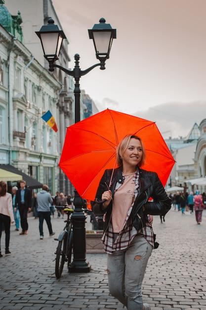 秋の市内中心部で赤い傘の下で若い陽気な女性 Premium写真