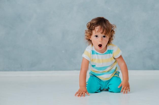 Смешной милый курчавый малыш сидит играющ в автомобиле на белом поле на заднем плане серой стены. Premium Фотографии