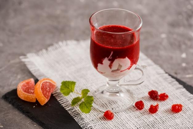 灰色の背景上のガラスに新鮮なイチゴのスムージー。 Premium写真
