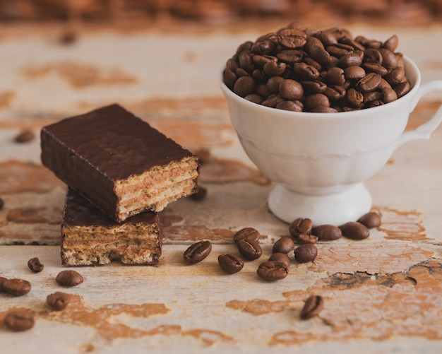 木製の背景に散在している穀物とコーヒーのカップ。チョコレートワッフル、甘いデザート Premium写真