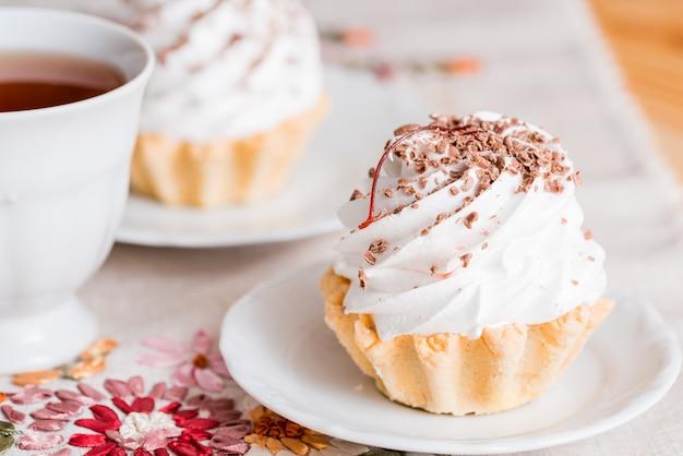 白いウッドの背景にバニラカップケーキ Premium写真